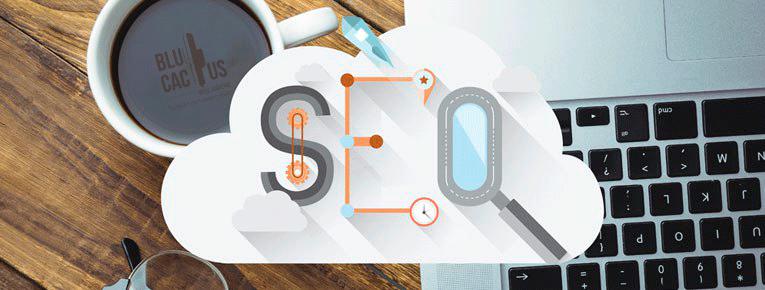 Una tasa de cafe que se refleja el logotipo de BluCactus. En el escritorio herramientas de SEO.