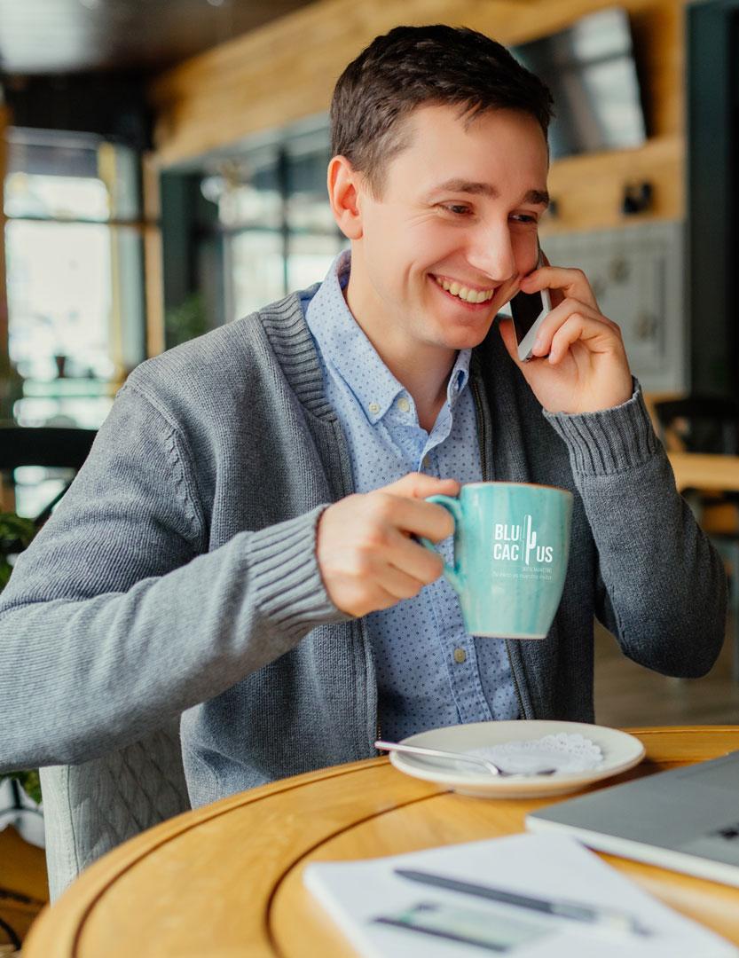 Un muchacho en un restaurante en su teléfono celular tomando chocolate caliente con una tasa con logotipo de BluCactus