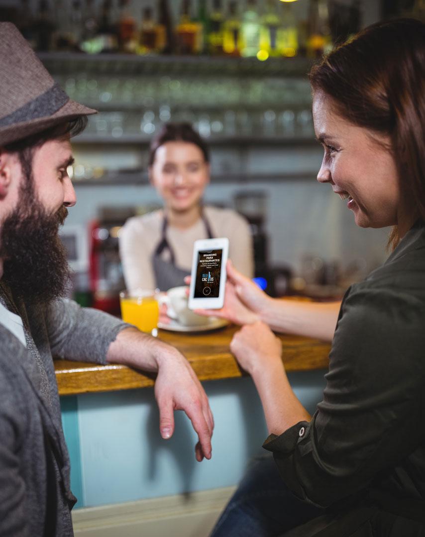 Una mujer le muestra un teléfono celular a un hombre con el logotipo de Blue Cactus mostrando el branding para restaurantes