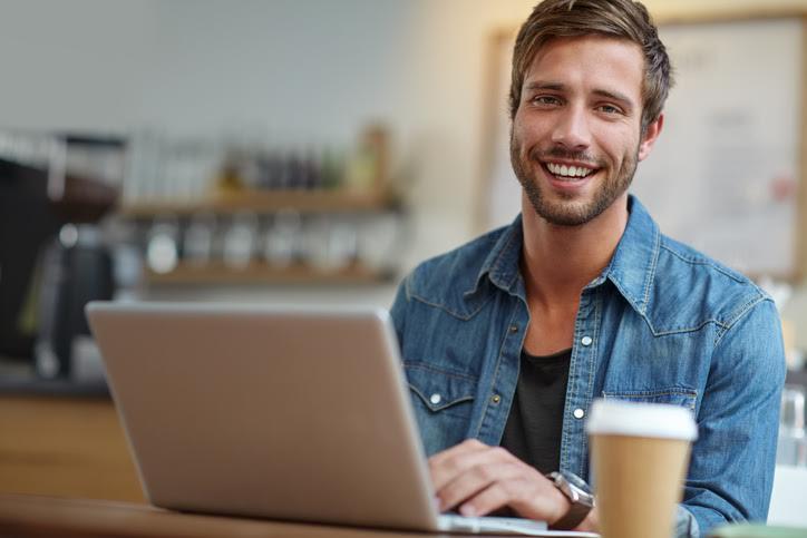 Retrato de un apuesto joven sentado con su computadora portátil en una cafetería escribiendo un blog como invitado